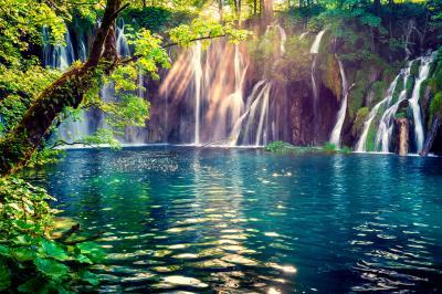 Fototapeta Last sunlight lights up the pure water waterfall on Plitvice National Park